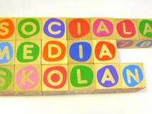 Träklossar med bokstäver som bildar orden Sociala media-skolan